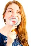 Menina com a lente de aumento que mostra seus dentes bonitos Imagem de Stock Royalty Free