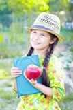 Menina com livro e maçã vermelha no dia de verão Fotografia de Stock