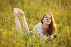 A menina com livro encontra-se na grama e no sonho Imagens de Stock Royalty Free