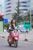 Menina com máscara protetora na e-bicicleta retro do projeto, Kunming, China Fotos de Stock Royalty Free