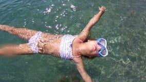 Menina com máscara que aprecia o mar e o sol video estoque