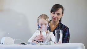 Menina com a mãe que faz a inalação com nebulizer filme