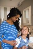 Menina com a mãe que guarda escovas de dentes no banheiro fotos de stock