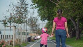 Menina com mãe Rollerblading em um parque filme