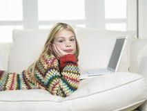 Menina com mão em Chin Using Laptop On Sofa imagem de stock