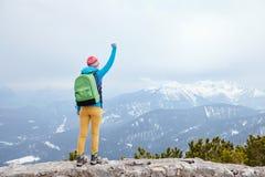 Menina com mão levantada nas montanhas Fotografia de Stock