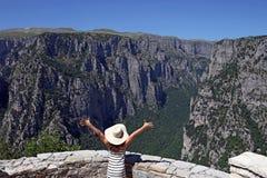Menina com mãos acima no desfiladeiro de Vikos do ponto de vista Fotos de Stock Royalty Free