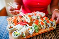 A menina com m?os bem arrumados guarda hashis para o sushi A menina come um grande grupo de sushi imagens de stock