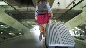 Menina com mala de viagem que anda no salão da estação filme