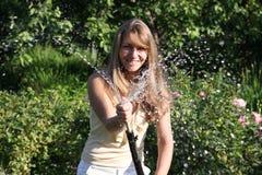 Menina com mangueira Foto de Stock Royalty Free