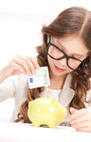 Menina com mealheiro e dinheiro Fotografia de Stock Royalty Free
