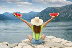 Menina com a melancia que senta-se perto do mar Fotos de Stock Royalty Free