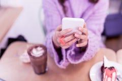 Menina com mensagens de datilografia do tratamento de mãos cor-de-rosa exato no smartphone fotos de stock
