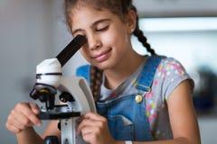 Menina com microscópio Foto de Stock Royalty Free