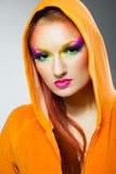 A menina com multi colorida compo e capa alaranjada Imagens de Stock Royalty Free