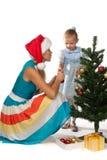A menina com mum decora uma árvore de Natal Imagens de Stock