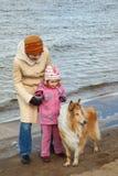A menina com mum e o cão andam na praia do outono Imagens de Stock Royalty Free