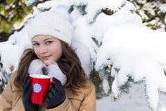 A menina com o ascendente perto do abeto vermelho ramifica na neve Fotos de Stock Royalty Free