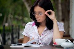 Menina com o bloco de notas no café fotos de stock royalty free