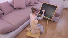 Menina com o brinquedo do coelho perto do quadro-negro video estoque