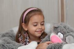 Menina com o brinquedo macio do gato Imagem de Stock