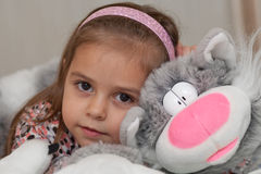 Menina com o brinquedo macio do gato Fotos de Stock Royalty Free