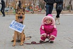 A menina com o cão com tabela traduzida dos amigos do ` do russo não dispara! ` na ação internacional para a proteção o Imagem de Stock Royalty Free