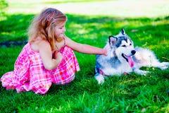 Menina com o cão do cão de puxar trenós siberian Fotografia de Stock