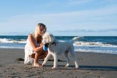 Menina com o cão na praia Fotos de Stock Royalty Free