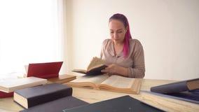 A menina com o cabelo cor-de-rosa está sentando-se na tabela que lê um livro video estoque