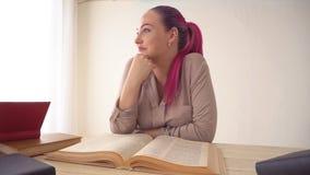 A menina com o cabelo cor-de-rosa está sentando-se na tabela que lê um livro vídeos de arquivo