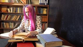 A menina com o cabelo cor-de-rosa nos livros de leitura da biblioteca video estoque