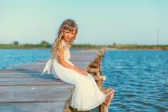 Menina com o cabelo louro longo que senta-se no cais Imagens de Stock Royalty Free