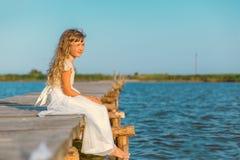 Menina com o cabelo louro longo que senta-se no cais Imagem de Stock Royalty Free