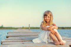 Menina com o cabelo louro longo que senta-se no cais Fotos de Stock