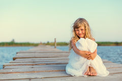 Menina com o cabelo louro longo que senta-se no cais Foto de Stock Royalty Free