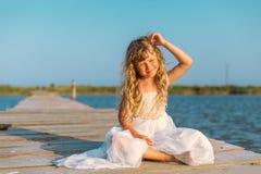 Menina com o cabelo louro longo que senta-se no cais Imagem de Stock