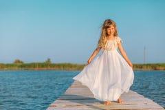 Menina com o cabelo louro longo que senta-se no cais Foto de Stock