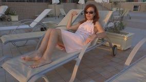 A menina com o cabelo vermelho bronzea-se no recurso pelo mar e pela piscina filme