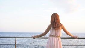 A menina com o cabelo vermelho olha no oceano video estoque