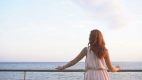 A menina com o cabelo vermelho olha no oceano vídeos de arquivo