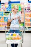 Menina com o carro completo do alimento no mercado imagens de stock
