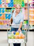 Menina com o carro completo do alimento no shopping fotografia de stock