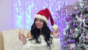 Menina com o chapéu de Santa com champanhe perto da árvore vídeos de arquivo