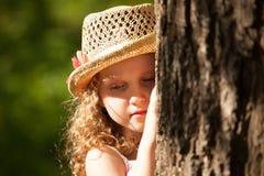 Menina com o chapéu que está perto da árvore no pensamento Fotografia de Stock