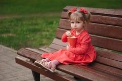 Menina com o copo da pipoca no parque imagem de stock royalty free