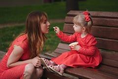 Menina com o copo da pipoca no parque Fotografia de Stock Royalty Free