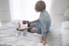 Menina com o copo em suas mão, chaleira e tabuleta em uma cama branca que olha na janela Fotos de Stock Royalty Free