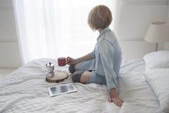 Menina com o copo em suas mão, chaleira e tabuleta em uma cama branca que olha na janela Imagens de Stock Royalty Free