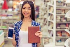 Menina com o dispositivo na livraria Imagens de Stock